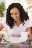 Woman in kitchen with newspaper and coffee smiling — Stock Photo