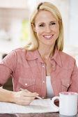 Mujer en cocina con periódico y café sonriendo — Foto de Stock