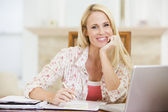 Woman in dining room with laptop frowning — Stock Photo