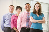 Business team standing indoors smiling — Stock Photo