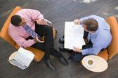 Dois empresários sentado dentro de casa com pasta e café portátil — Foto Stock