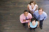 Four businesspeople standing indoors smiling — Stock Photo