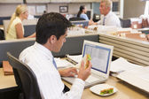 Businessman in cubicle at laptop eating sandwich — ストック写真
