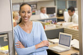 Businesswoman standing in cubicle smiling — Stockfoto