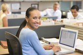 Businesswoman in cubicle using laptop smiling — Stock Photo