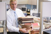 Businessman standing in cubicle holding stacks of files — Stock Photo