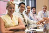 Five businesspeople at boardroom table smiling — Stock Photo