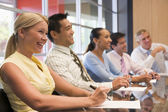Five businesspeople at boardroom table smiling — Foto de Stock