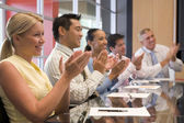 Five businesspeople at boardroom table applauding and smiling — Stock Photo
