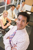 Businessman with four businesspeople at boardroom table in backg — Stock Photo