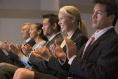 Five businesspeople applauding and smiling in presentation room — Stockfoto