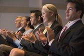 Vijf ondernemers applaudisseren en lachend in presentatieruimte — Stockfoto