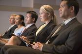 Vijf ondernemers zitten in presentatieruimte met klemborden — Stockfoto