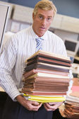 Businessman standing in cubicle with stacks of files — Stock Photo