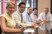 Five businesspeople in boardroom smiling — Stock Photo