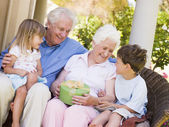 Grandparents with grandchildren on patio with gift smiling — Stock fotografie