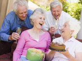 Two couples on patio with cake and gift smiling — Stock Photo