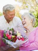 Man vrouw bloemen buitenshuis glimlachend geven — Stockfoto