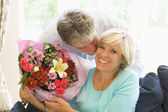 Husband giving wife flowers kissing and smiling — Stock Photo