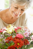 Woman with flowers smiling — Stock Photo