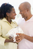 Husband and wife holding gift smiling — Stock Photo