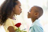 Young boy giving young girl rose and smiling — Stock Photo