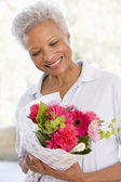Woman holding flowers and smiling — Stok fotoğraf