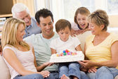 Family in living room smiling with young boy blowing out candles — Stock Photo