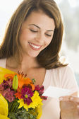 Woman holding flowers and reading note smiling — Stok fotoğraf