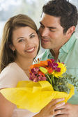 Husband and wife holding flowers and smiling — Stockfoto