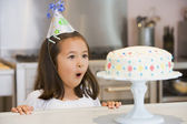 Young girl wearing party hat at kitchen counter looking at cake — Stock Photo