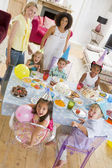Young children at party with mothers sitting at table with food — Stock Photo