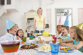 Young children at party sitting at table with mother carrying ca — Stock Photo