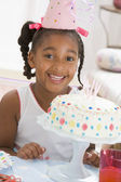 Young girl wearing party hat with cake in front of her smiling — Stock Photo
