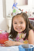 Young girl wearing party hat at table smiling — Stock Photo