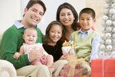 Familie met nieuwe geboren, zittend op bank, houden de gift van kerstmis — Stockfoto