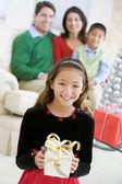 Ung flicka stående anläggning julklapp, med sina föräldrar en — Stockfoto