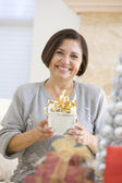 Woman Sitting On Sofa Holding A Christmas Gift — Stock Photo