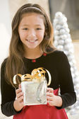 Young Girl Smiling,Holding Christmas Gift — Stockfoto
