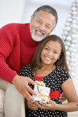 Grandfather Giving His Granddaughter A Christmas Present — Stock Photo