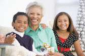 Grandmother Sitting With Her Two Grandchildren,Holding A Christm — Stock Photo