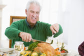 Man Carving Up Turkey At Christmas Dinner — Stock Photo