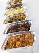 Selectie van indiase gerechten in folie containers meenemen — Stockfoto