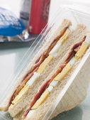 Egg And Bacon Sandwich On White Bread With A Bag Of Crisps And A — Stock Photo