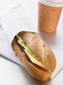 Baguette formaggio, sottaceti e insalata di formaggio cheddar con un take away coffe — Foto Stock