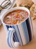 Cup Of Vegetable And Pasta Soup With A Granary Bread Roll — Stock Photo