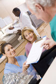 Nurses Being Handed A Clipboard At The Reception Area In A Hospi — Stock Photo
