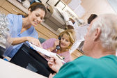 Nurses Discussing A Clipboard At The Reception Area In A Hospita — Stockfoto