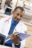 A Doctor Writing On A Clipboard At The Reception Area Of A Hospi — Stock Photo