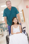 An Orderly Pushing A Little Girl In A Wheelchair Down A Hospital — Stock Photo